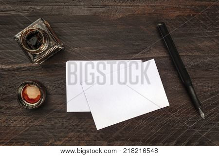 An overhead photo mockup of blank white business cards on a dark wooden background texture with vintage stationery, a presentation template with a nib pen, ink, and a place for text