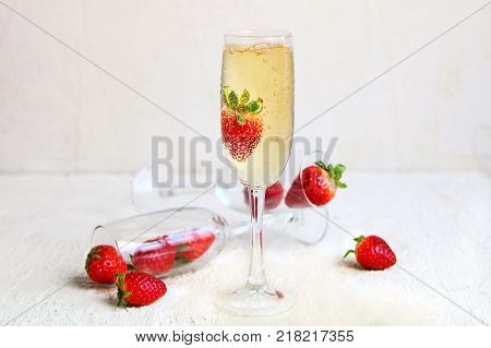 a crystal glass of champagne with fresh strawberries