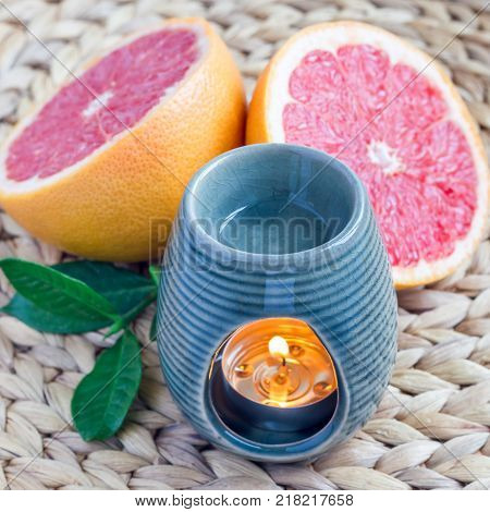 Aroma lamp with grapefruit essential oil on woven mat grapefruits on background square format