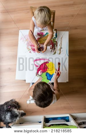 High angle view of two children panting with colorful paints in room with dog.