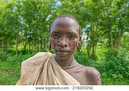 SOUTHWESTERN ETHIOPIA - MAY 3, 2015 : Portrait of a young boy from the african tribe Suri with traditionally enlarged Ears