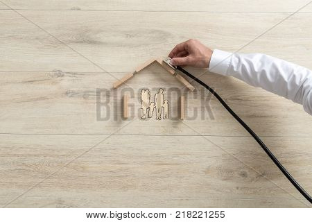 High-angle conceptual close-up of the hand of an expert holding a stethoscope on the roof of a family house made of building wooden blocks.
