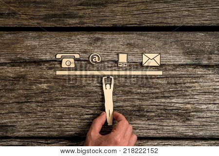 Business communications and contact concept with a businessman supporting a cut out of a man holding up a line of phone web and mail icons on rustic wood.
