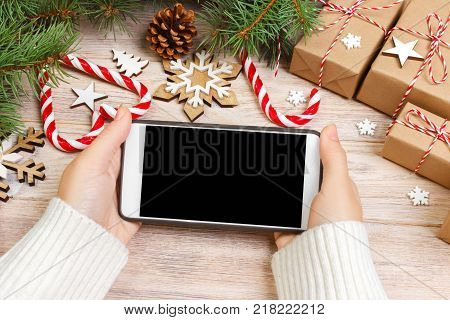 Christmas online shopping. Female buyer makes order at screen of smartphone with copy space. Woman buys presents for xmas eve sits at home near decorated. Winter holidays sales.