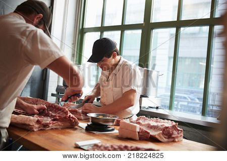 Two butchers cutting meat to sell at a butcher's shop