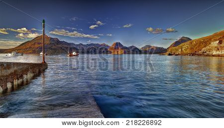 Elgol pier. Elgol peninsula on the beautiful Isle of Skye looking towards Torrin and the Cuillin mountains. Afternoon sunlight lit up this mountains in october poster