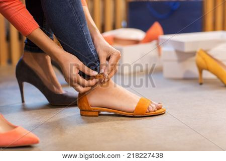 sale, shopping, fashion and people concept - young woman trying sandals at shoe store