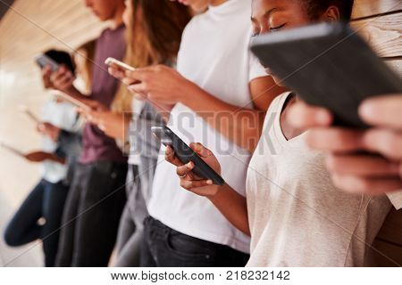 Teenage Students Using Digital Devices On College Campus