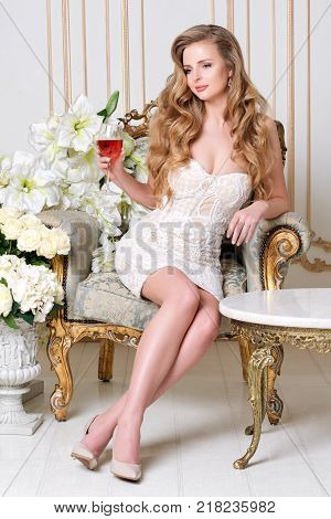 Elegant blonde lady with glass of wine in restaurant. Beautiful sexy young woman with long hair perfect body and pretty face make-up wearing blue dress drinking alcohol in light luxury interior
