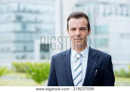 Portrait of handsome unsmiling businessman standing outdoors