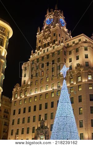 Madrid, Spain - December 12, 2017. Telefonica building in Gran Via street of Madrid with a shinny christmas tree in foreground.