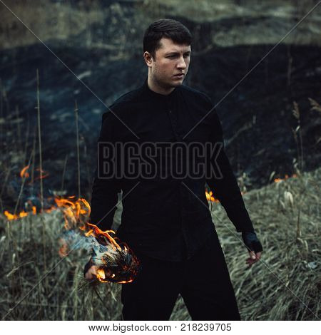 a handsome man with a torch in his hands burns. The guy brings trouble to nature. Ecology. Dressed in a black shirt