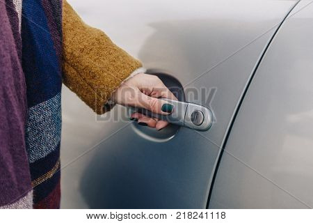 partial view of woman holding car door handle