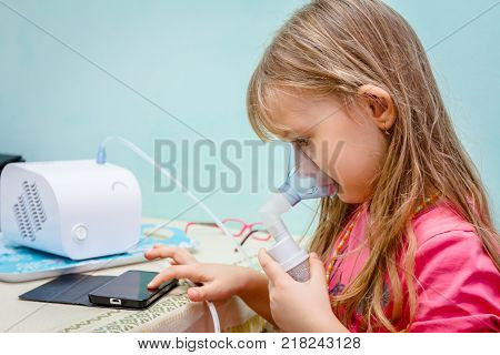 Child is take inhalation with mask on her face and play games with her phone.