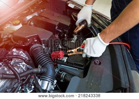 Mechanic using jumper cables to start a car