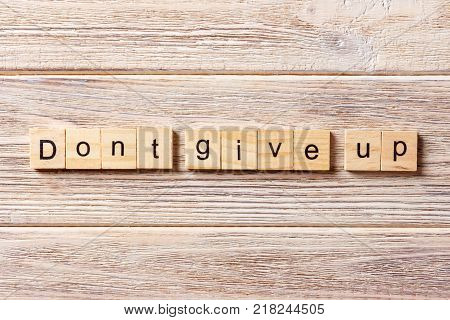 Dont give up word written on wood block. Dont give up text on table concept.