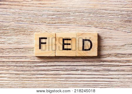 FED word written on wood block. FED text on table concept.