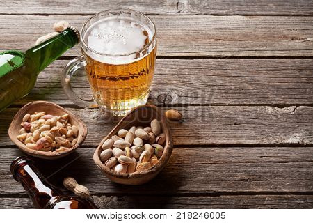 Lager beer and snacks on wooden table. Various nuts. With copy space poster