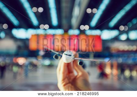 Hand is holding model airplane against arrival and departure board in a airport terminal.