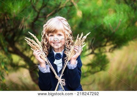 First-grader in the background of the autumn park. A schoolgirl with blond curls holds a pile of ears in her hands and peeks out from behind her. Day of knowledge, the beginning of the school year