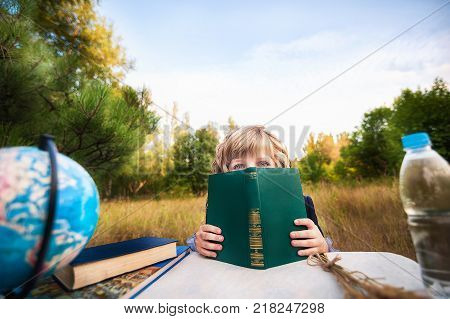 A first grader sitting at a table in the background of an autumn park and a green Christmas tree. Schoolgirl with blond curls. Day of knowledge, the beginning of the school year, a farewell call. Glob