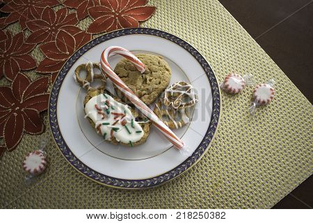 Cookies and other sweet goodies are arranged on a white plate on top of gold mat with red poinsettia cloth beside.