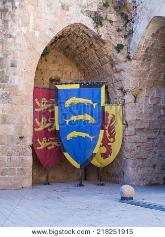 Acre Israel November 03 2017 : Knightly flags with coats of arms displayed in the ruins of the fortress in the old city of Acre in Israel