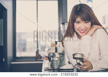 small business owner standing at counter in coffee shop. asian female barista smiling at bar in cafe. food service, restaurant concept.