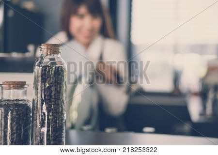 small business owner standing at counter in coffee shop. asian female barista wearing apron smiling at bar in cafe. food service, restaurant concept.