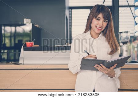 small business owner holding notebook at counter in coffee shop. asian female barista writing note at bar in cafe. food service, restaurant concept.