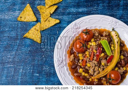Traditional Mexican chili con carne on the table with vegetables and nachos. Selective focus.