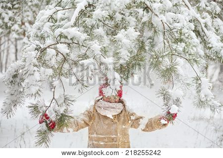 Beautiful little girl wearing a beige down jacket and red knitted hat and scarf playing in a snowy winter park on Christmas day. Child playing with snow in winter. Kids play and jump in snowy forest
