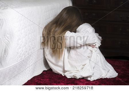 image covering the Social Issues of child abuse Young unrecognisable girl is a affluent bedroom curled in to a ball hugging her legs copy space for text