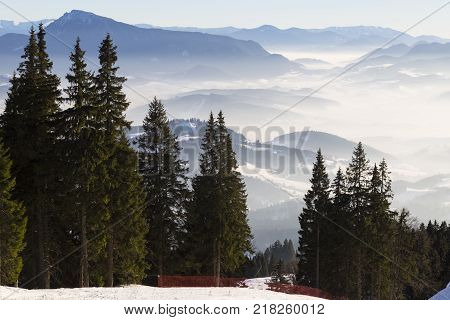 Top view from the ski slopes among the spruces on snow covered and foggy valley on the background mountain peaks. Skiing park Kubinska Hola; Western Tatras. Slovakia. Travel destination for winter vacations .