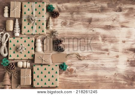 Above view of brown Christmas present boxes in arrangement, with sparkling embossed fur trees, pine cones, golden baubles, wooden decorations, jute twine, copy space for text