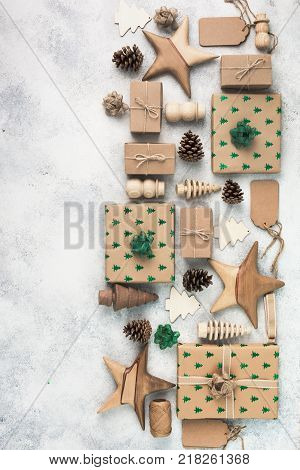 Christmas arrangement, brown present boxes with embossed fir trees, pine cones, brown gift tags, wooden decorations, jute twine, top view, on the light background, copy space for text, vertical