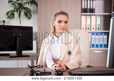 Portrait of Callcenter support beautiful blonde woman operator at her desk looking at the camera