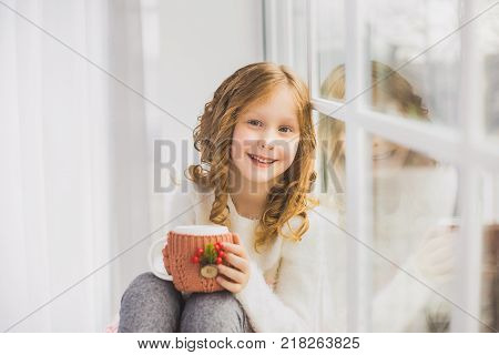 Portrait of cute happy little girl sitting on windowsill drinking hot tea and looking outside from window. Child holding white mug in winter knitted cover festively decorated