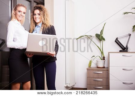 Businesswoman holding a laptop in hands next to her work colleague in office enviroment