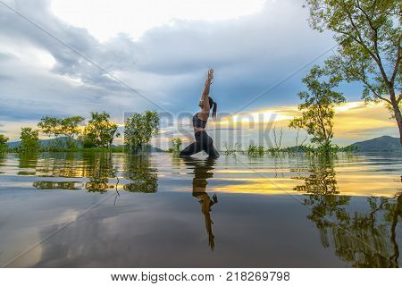 Silhouette young woman lifestyle exercising vital meditate and practicing reflect on water Flood the tree in the reservoir background sunset. Healthy Concept.