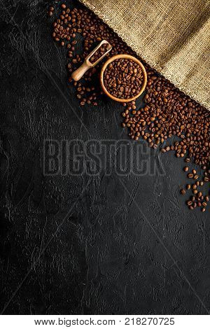 Coffee background. Roasted beans on black table top view.