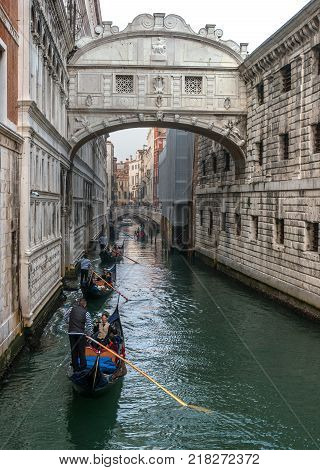 Venice, Italy - October 13, 2017: Gondolas with tourists swim under the Bridge of Sighs. Bridge of Sighs joins the palace of the Doges and the medieval prison.