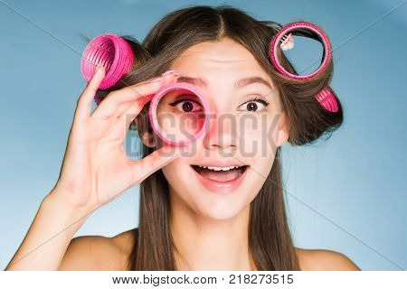 happy young girl wants a beautiful hairstyle, on her head big curlers