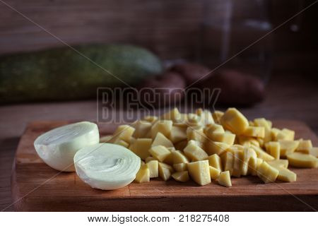 two halves of onions on the background of chopped potatoes on a cutting board