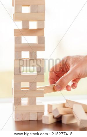 The tower from wooden blocks and man's hand take one block