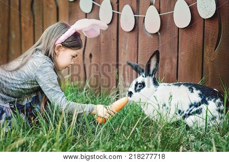 Children Play With Real Rabbit. Laughing Child At Easter Egg Hunt With White Pet Bunny. Little Toddl