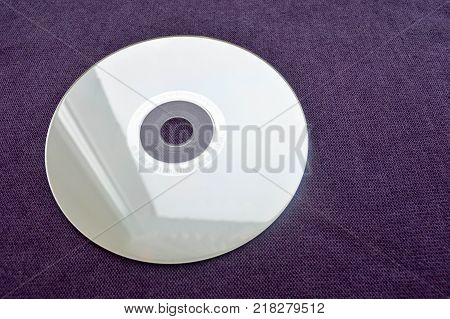 Brilliant compact disc. CD DVD Bluray disc on a violet background.