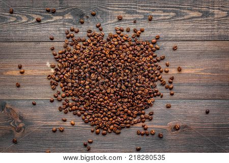 Scattered coffee beans on dark wooden table top view. Coffee background