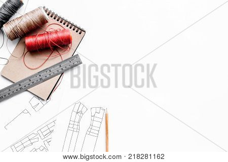 Tailor's work desk. Pattern of clothing and tools on white background top view.