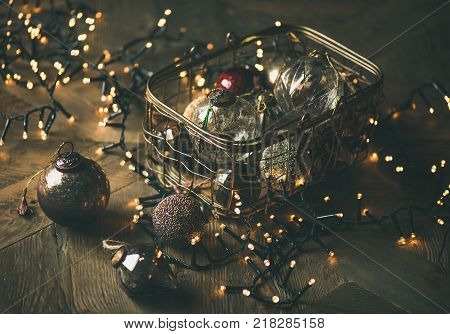 Christmas or New Year background, preparing for holiday. Christmas tree toy decoration balls in vintage box and light garland over rustic wooden background, selective focus
